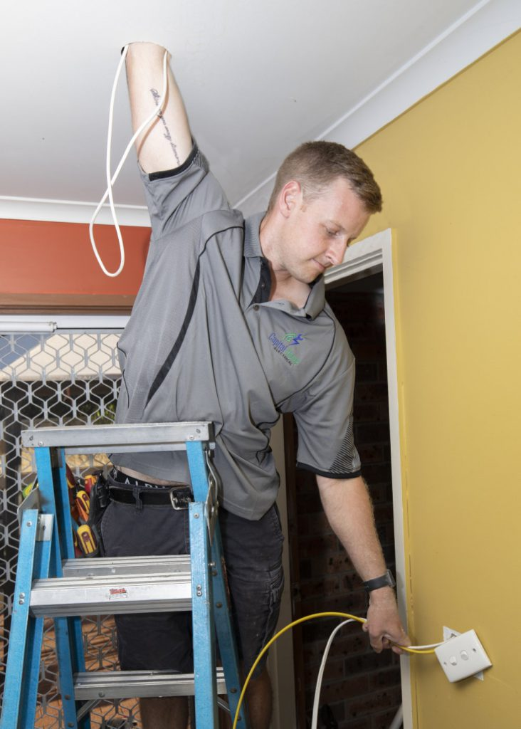 Electrician on a ladder fixing cabling